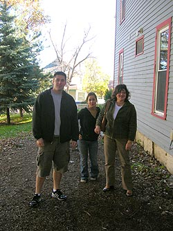 Three people standing beside a house
