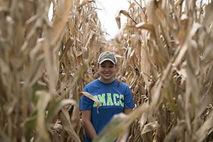 student standing in cornfield