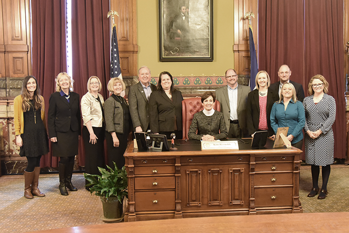 DMACC Court Reporting Week 2019, photo of court reporting staff and faculty standing around Governor Kim Reynolds desk